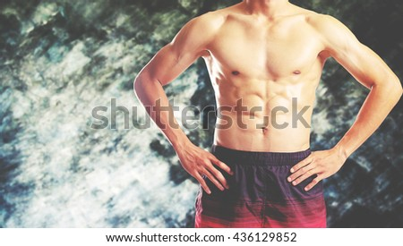 Awesome bodybuilder showing his Muscles and posing on old grunge wall. Vintage effect. - stock photo