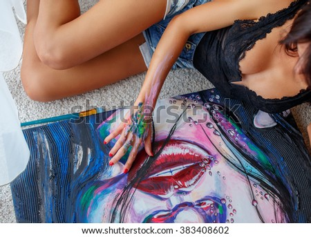Awesome brunette woman in denim shorts sitting on the floor and painting a face. - stock photo
