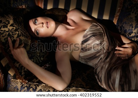 Awesome brunette woman lying on a sofa in deep shadows.