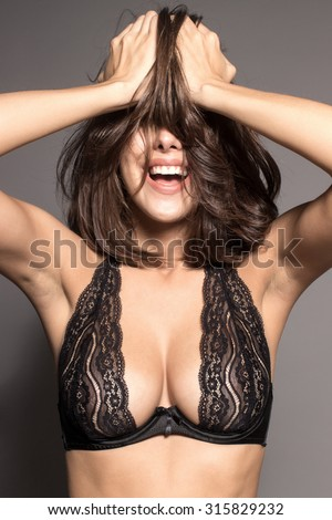 Awesome Caucasian attractive joyful happy sexy female model is shaking head with brunette hair in studio wearing black transparent lingerie, isolated on gray background - stock photo