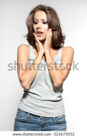 Awesome Caucasian attractive joyful happy sexy female model with brunette hair is grimacing in studio, wearing grey sleeveless shirt, isolated on white background - stock photo