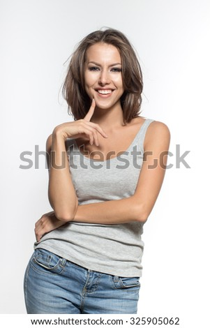 Awesome Caucasian attractive joyful happy sexy female model with brunette hair is grimacing in studio, wearing grey sleeveless shirt and jeans, isolated on white background - stock photo