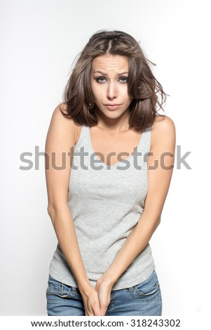 Awesome Caucasian attractive sad female model with brunette hair is grimacing in studio, wearing gray sleeveless shirt, isolated on white background - stock photo