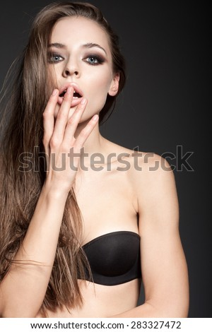 Awesome caucasian attractive sexy fashion model with long brunette natural hair, beautiful eyes, full lips, perfect skin posing  in studio, touching shoulders, beauty photo shoot, retouched image - stock photo