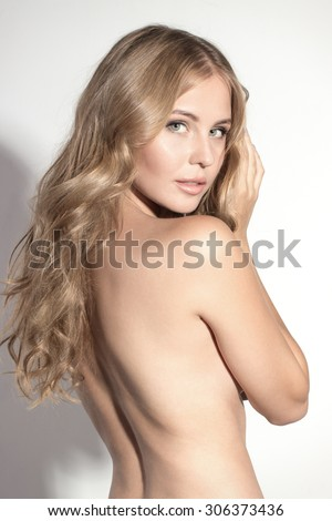 Awesome caucasian attractive sexy professional female model with blond hair posing in studio topless, perfect make up, turning head, isolated on white background - stock photo