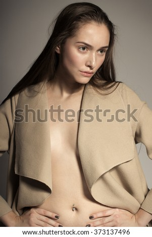 Awesome European attractive sexy fashion model with natural brunette hair, long eyelashes, full lips, perfect skin, posing in studio, wearing beige coat, beauty photo shot, retouched image - stock photo