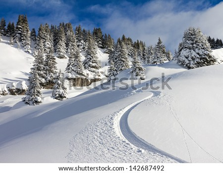 Awesome first track on a sunny powder day in Les Portes du Soleil in the European alps - stock photo