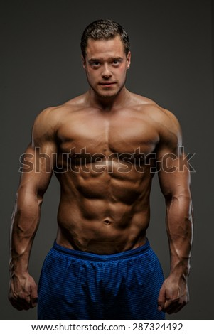 Awesome muscular guy in blue shirts showing his muscles. Isolated on grey background