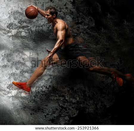 Awesome muscular male in a jump with basket ball in a hand. Grey background. - stock photo