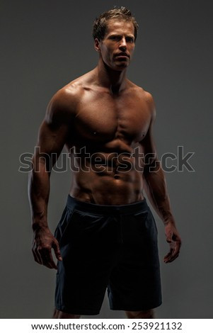Awesome muscular male in black shorts with naked torso. Isolated on grey background. - stock photo