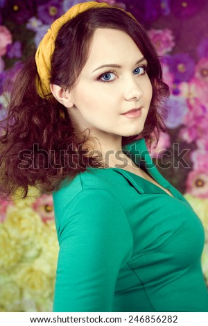 Awesome portrait of brunette girl in green dress and blue eyes with flowers background - stock photo