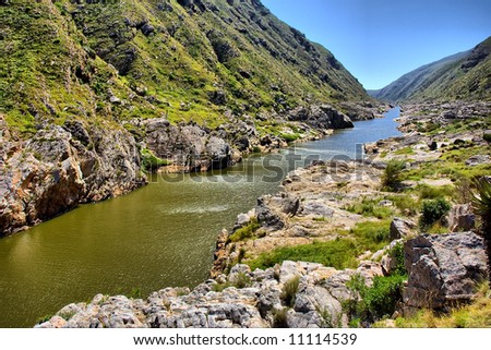 Awesome river in mountains against sun. Shot in the Langeberge highlands next to the Gouritsrivier river, Garden Route, Western Cape, South Africa. - stock photo