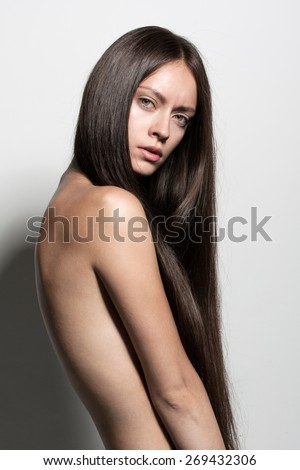 Awesome sexy fashion model with long brunette natural hair, beautiful eyes, full lips, perfect skin posing topless in studio without make-up for beauty photo shoot, retouched image - stock photo