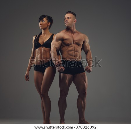 Awesome sporty couple. Shirtless bodybuilder and athletic brunette woman in black underwear.. Isolated on grey background. - stock photo