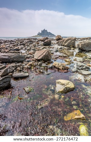 Awesome St Michaels mount in cornwall england uk. With a foreground of rocks looking from the harbour at Marizion. - stock photo