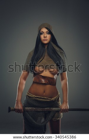 Awesome woman with long black hair in ancient knight clothes holding sword. Isolated on grey background. - stock photo
