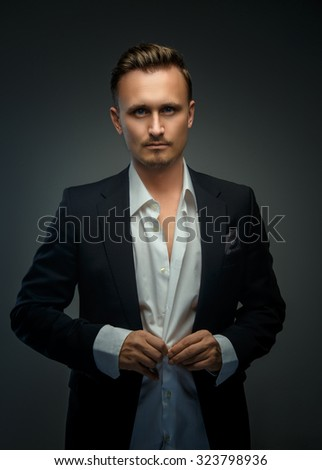 Awesome young businessman in white shirt and black suit posing in studio on grey background.