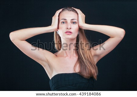 Awful headache. Pretty woman holding head in hands standing against black background - stock photo