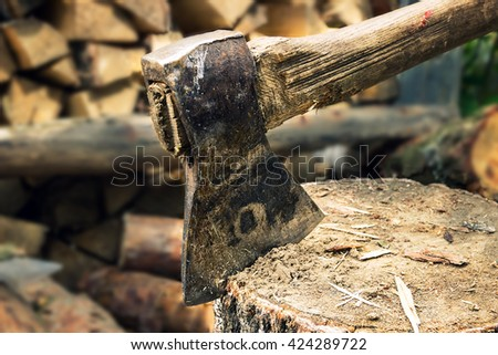 ax, hatchet, axe. split a log with an ax. birch  firewood in the background. wood wallpaper - stock photo