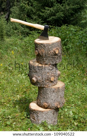 Axe and four stubs on a green lawn in wood - stock photo
