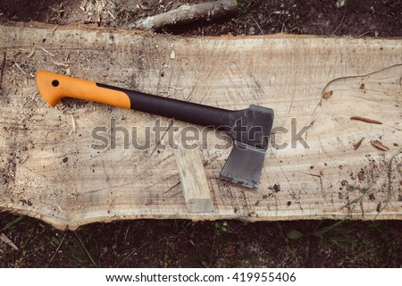 Axe on wood. Woodworking tool and wooden background. Axe in wood, chopping timber. Lumberjack axe in wood. Big forest axe on wood background. Travel, adventure, camping gear, outdoors items. - stock photo