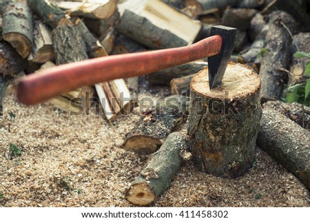 Axe stuck in a stump on a background of chopped firewood.