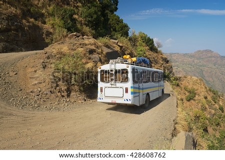 AXUM, ETHIOPIA - JANUARY 23, 2010: Tourist bus pass by the gravel mountain road in Axum, Ethiopia.