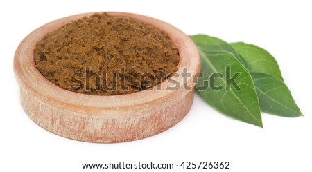 Ayurvedic henna leaves with paste in a wooden bowl