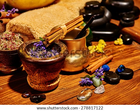 Ayurvedic spa massage still life with candle and blue small flower. - stock photo