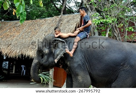 Ayutthaya, Thailand - December 22, 2010:  Thai father with his naked toddler son riding atop an elephant at the Ayutthaya Elephant Royal Palace & Kraal - stock photo