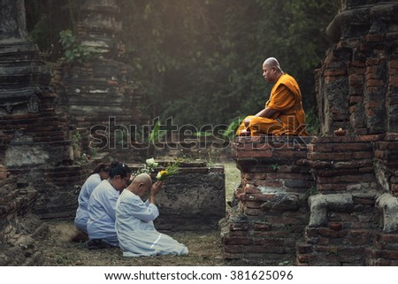 Ayutthaya, Thailand - February 22, 2016: People praying respect to monk on Ayutthaya. Roughly 95% of the Thai people are practitioners of Theravada Buddhism, the official religion of Thailand - stock photo