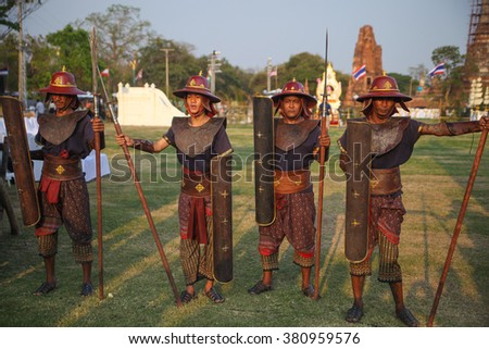 AYUTTHAYA,THAILAND - MARCH 17,2013 : Ancient Thailand warriors in historical armor with shields and spears on background of stupas Wat Phutthaisawan at Ayutthaya old city