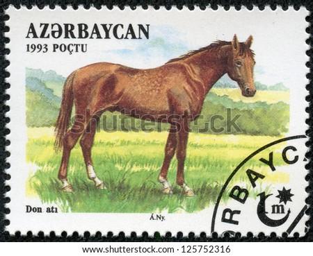 AZERBAIJAN - CIRCA 1993: A stamp printed in Azerbaijan shows a brown, Akhal-Teke Akhaltekin breed horse standing in a pasture, circa 1993. - stock photo