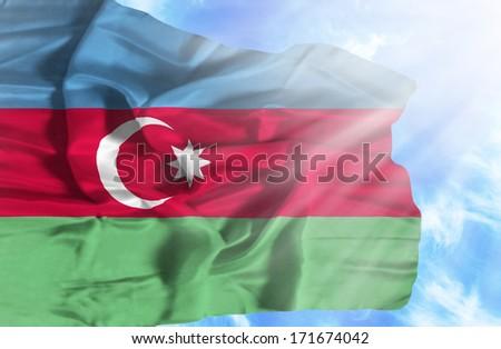 Azerbaijan waving flag against blue sky with sunrays - stock photo