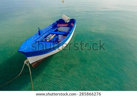 Azure blue motor boat is floating on calm transparent sea water on Greek Kos island - stock photo
