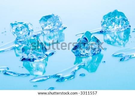 Azure colored ice cubes melted in water on reflection surface ready to be added to a cocktail