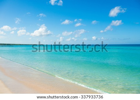 Azure turquoise calm sea, clear blue sky, sandy beach and flat horizon - stock photo