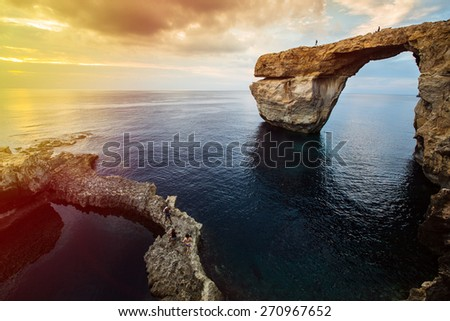 Azure Window, natural arch, famous landmark and popular tourist spot, on Gozo island, Malta, Mediterranean, at dramatic sunset. People walking on top of it, restricted area.  - stock photo