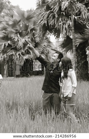 B&W / Cheerful young newlyweds hugging tenderly in bright countryside - stock photo