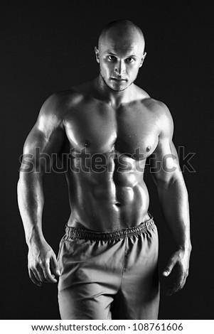 B&W Muscular male bodybuilder on black background - stock photo