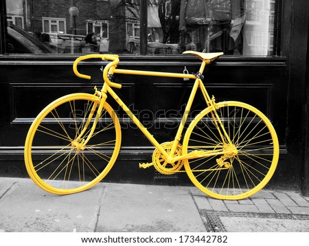 b&w photo of old yellow bike on the window of the coffee shop        - stock photo