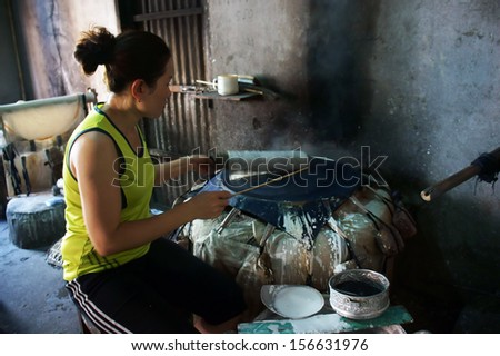 BA RIA, VIET NAM- FEBRUARY 2 .Woman make girdle cake (banh trang) - is the usual rice flour's cake of Viet Nam- at trational trade village, Ba Ria, February 2, 2013