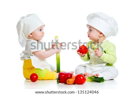 babies boy and girl wearing a chef hat with healthy  food vegetables - stock photo