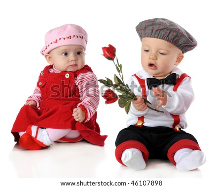Babies dressed up for Valentine's Day.  The boy holds long stemmed roses while the girl looks on. - stock photo