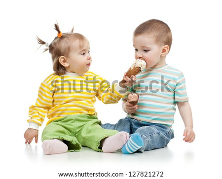 babies girl and boy eating ice cream together in studio isolated - stock photo
