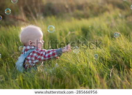 Babies reach for a soap bubbles on a grass - stock photo