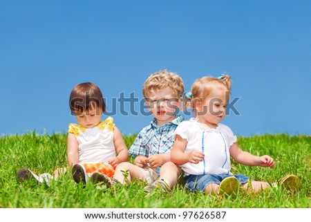 Babies sit on grass against blue sky - stock photo
