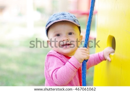 baby age of 10 months on playground in summertime