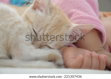 Baby and cat nap sleeping together on white sheet - stock photo