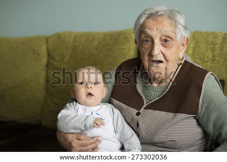 Baby and elderly woman looking at camera with surprised expression - stock photo